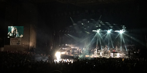 A costumed silver man rises above the crowd during Arcade Fire's Xfinity Center concert